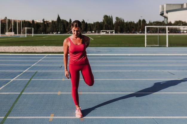 Młody blondynki sprawności fizycznej kobiety biegacz rozciąga nogi na stadium błękita śladzie przy zmierzchem. pojęcie sportu i zdrowego stylu życia