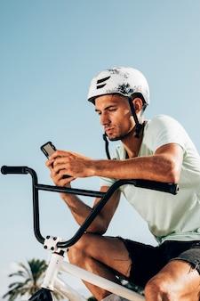 Młody bmx jeździec patrzeje telefonu środka strzał