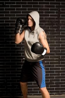 Młody bokser ćwiczący podczas treningu stojąc przed ciemną ceglaną ścianą
