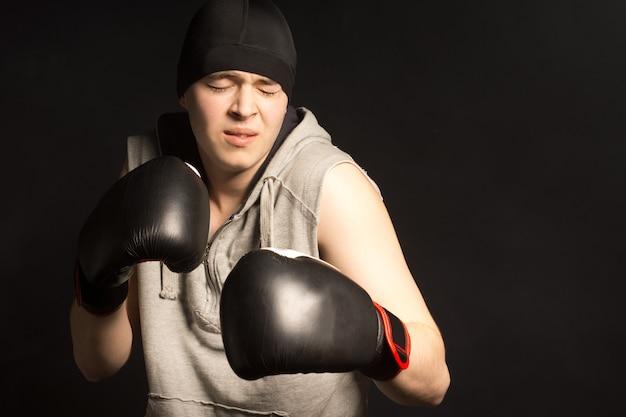 Młody bokser krzywiący się z bólu, gdy stoi z uniesionymi w ciemności pięściami w rękawiczkach