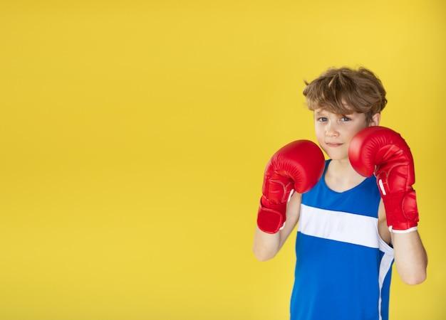 Młody bokser na kolor żółty ścianie