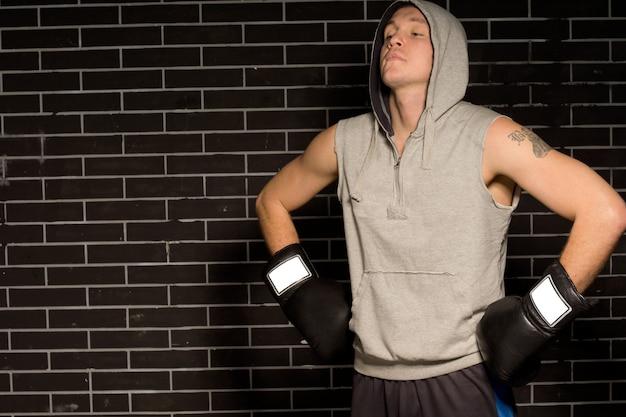 Młody bokser robi ćwiczenia oddechowe przed walką