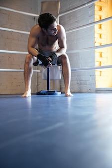 Młody bokser siedzi w rogu ringu