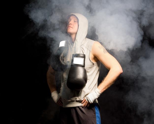 Młody bokser stojący w zadymionej atmosferze oddycha głęboko, by uspokoić nerwy