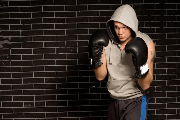 Młody bokser trenujący do walki przykucnięty