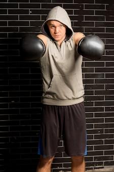 Młody bokser uderza pięściami w rękawiczkach w stronę kamery