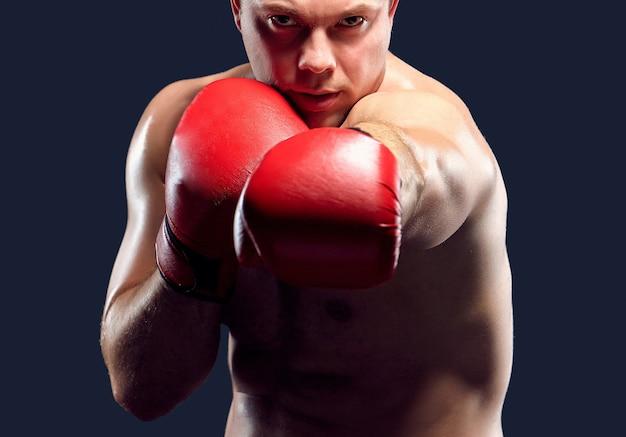 Młody bokser w czerwonych rękawiczkach boksuje na czarnym tle