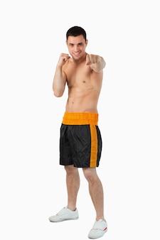 Młody bokser z gołymi pięściami uderzającymi prosto