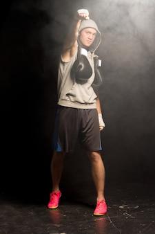Młody bokser z salutem energetycznym uderza w powietrze