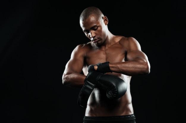 Młody bokser zakładający rękawice bokserskie przed treningiem