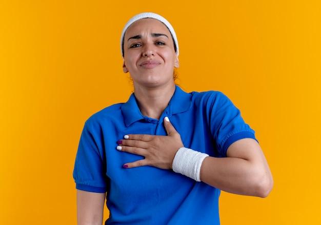 Młody bolący kaukaski kobieta sportowy noszący opaskę i opaski na nadgarstek kładzie rękę na klatce piersiowej na białym tle na pomarańczowej przestrzeni z miejsca na kopię