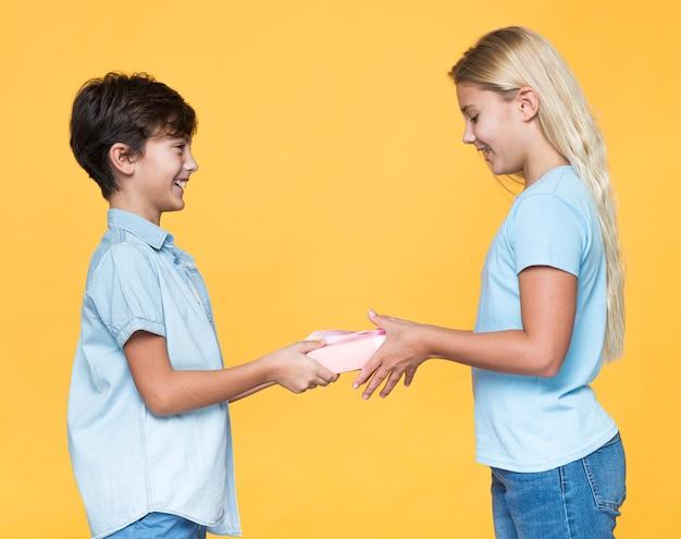 Młody brat oferuje prezent siostrze