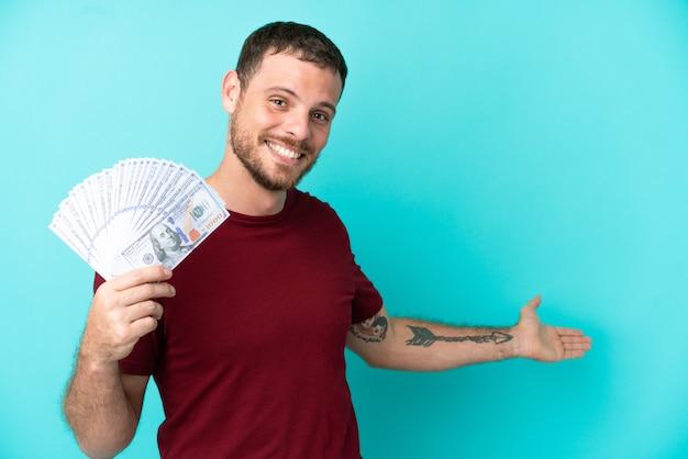 Młody brazylijczyk biorący dużo pieniędzy na odosobnionym tle, wyciągając ręce do boku za zaproszenie do przyjścia