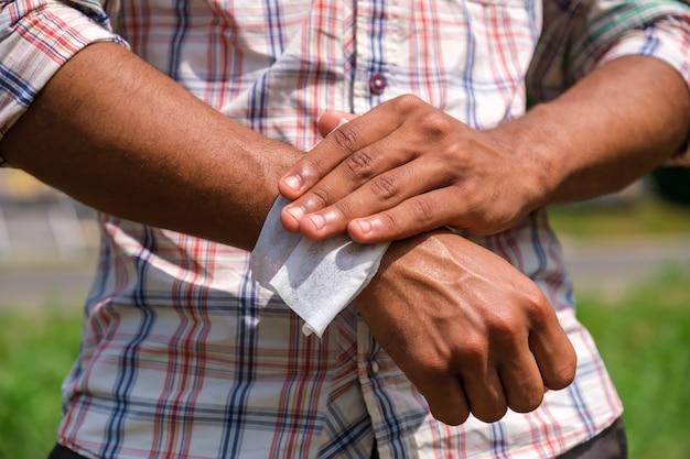 Młody brazylijczyk dezynfekuje ręce za pomocą mokrej chusteczki z bliska, aby zapobiec infekcji na zewnątrz w parku w lecie