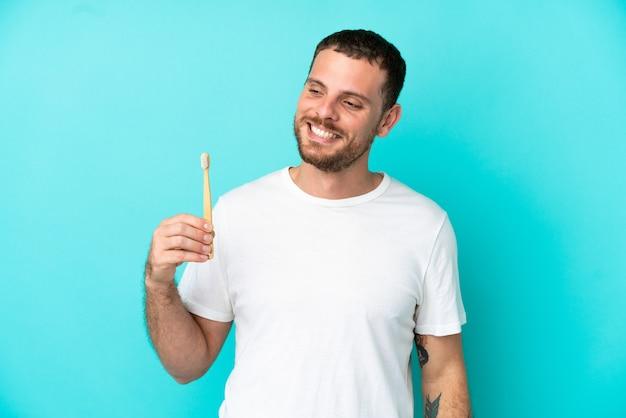 Młody brazylijczyk myje zęby na białym tle na niebieskim tle, patrząc w bok i uśmiechając się