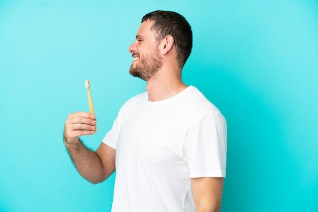 Młody brazylijczyk myje zęby na białym tle na niebieskim tle, śmiejąc się w pozycji bocznej