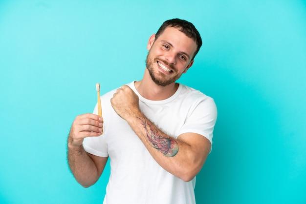 Młody brazylijczyk myje zęby na białym tle na niebieskim tle świętuje zwycięstwo
