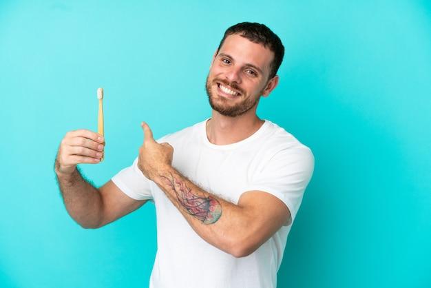 Młody brazylijczyk myje zęby na białym tle na niebieskim tle, wskazując do tyłu