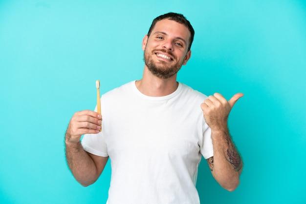 Młody brazylijczyk myje zęby na białym tle na niebieskim tle, wskazując na bok, aby zaprezentować produkt