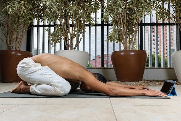 Młody brazylijczyk przygotowuje się do rozpoczęcia zajęć jogi online, w pozie dziecka.