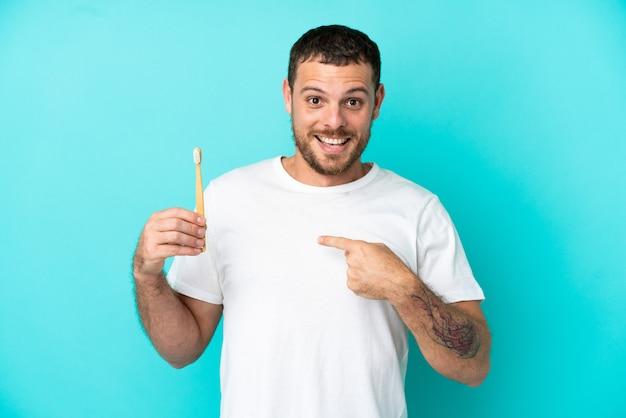 Młody brazylijczyk szczotkuje zęby na białym tle na niebieskim tle z niespodzianką wyrazem twarzy