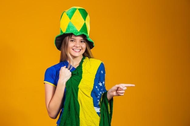 Młody brazylijski fan wskazujący na bok z miejscem na tekst