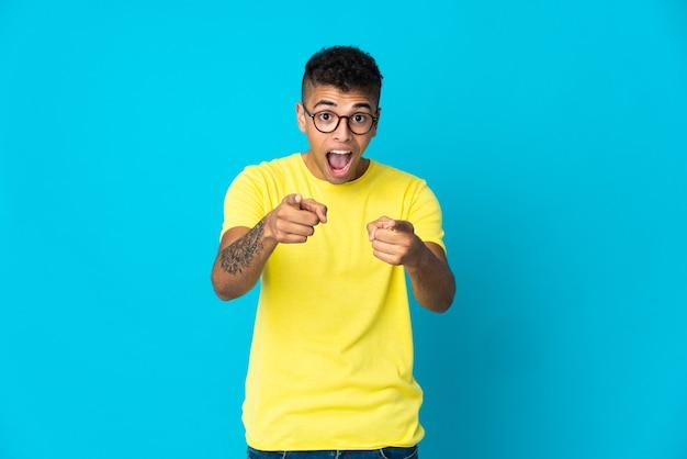 Młody brazylijski mężczyzna na białym tle na niebieskiej ścianie zaskoczony i wskazujący przód