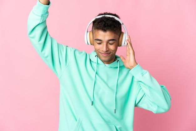 Młody brazylijski mężczyzna na białym tle słuchania muzyki i tańca