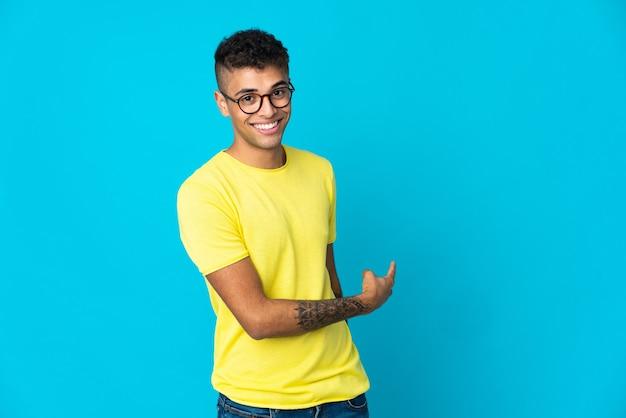 Młody brazylijski mężczyzna na niebieskim tle, wskazując wstecz