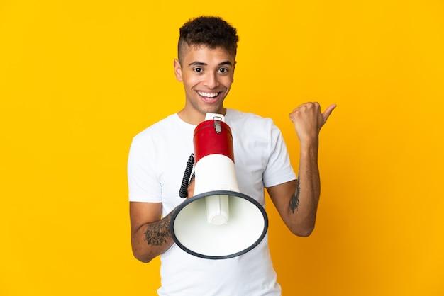Młody brazylijski mężczyzna na odosobnionej ścianie krzycząc przez megafon i wskazując stronę