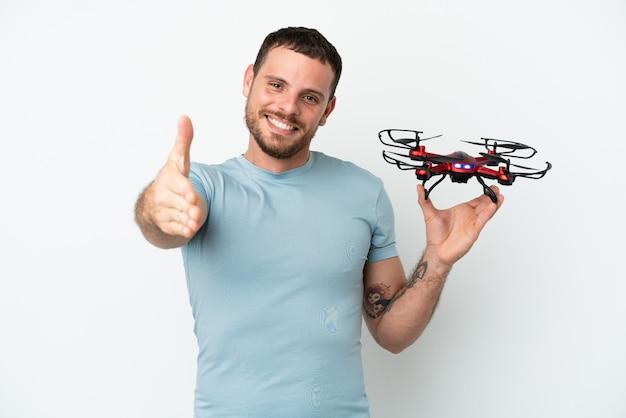 Młody brazylijski mężczyzna trzyma drona na białym tle, ściskając ręce, aby zamknąć dobrą ofertę