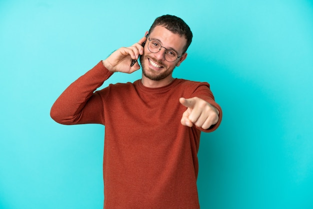 Młody brazylijski mężczyzna używający telefonu komórkowego na białym tle na niebieskim tle wskazujący przód ze szczęśliwym wyrazem twarzy