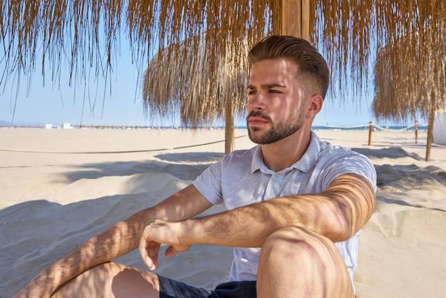 Młody broda człowiek na plaży pod parasolem