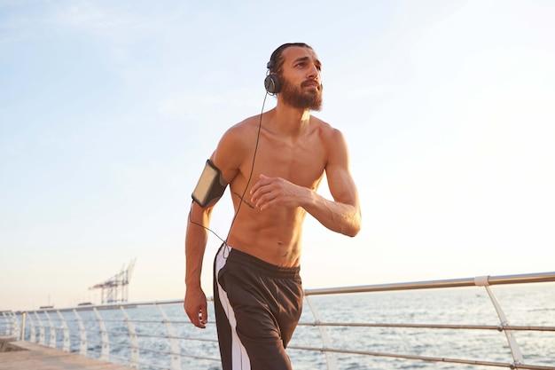 Młody brodacz biega nad morzem, słucha ulubionych piosenek na słuchawkach, cieszy się porankiem i życiem, prowadzi zdrowy, aktywny tryb życia.