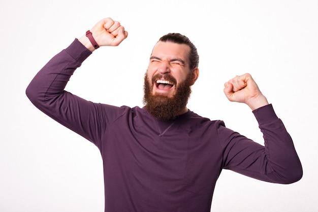 Młody brodacz jest bardzo podekscytowany, krzyczy i trzyma obie ręce w pobliżu białej ściany