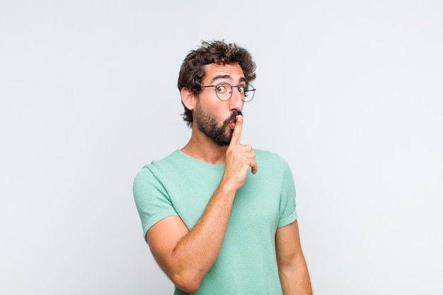 Młody brodacz prosi o ciszę i spokój, macha palcem przed ustami, mówi cii lub zachowuje tajemnicę