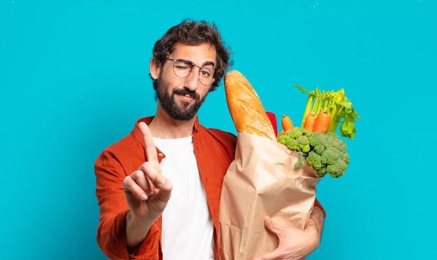 Młody brodacz uśmiecha się dumnie i pewnie, wykonując triumfalną pozę numer jeden, czując się jak przywódca i trzymając worek z warzywami
