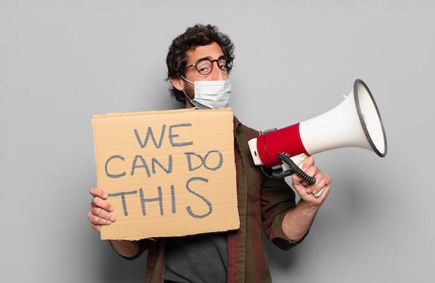 Młody brodacz w masce medycznej, trzymający afisz z tekstem: damy radę