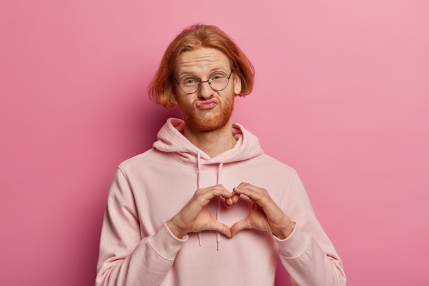 Młody brodacz wydyma usta i robi gest serca na piersi, nosi swobodną bluzę, wyraża uczucia, współczucie i miłość, ma rude włosy, jest zakochany w kobiecie, odizolowany na różowo