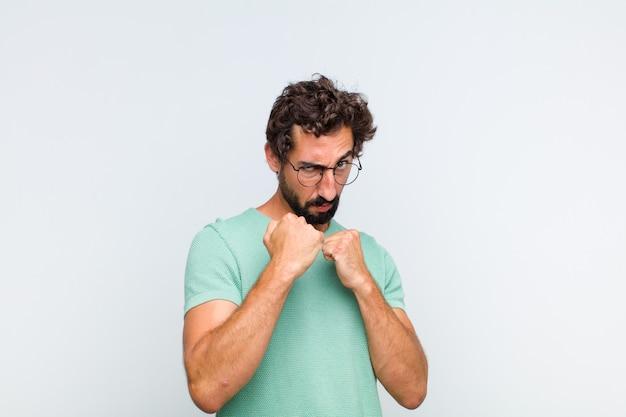 Młody brodacz wyglądający na pewnego siebie, wściekłego, silnego i agresywnego, z pięściami gotowymi do walki w pozycji bokserskiej