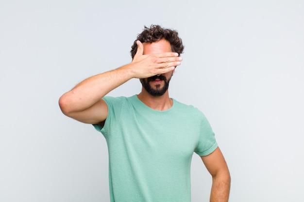 Młody brodacz zakrywający oczy jedną ręką, czując strach lub niepokój, zastanawiając się lub na ślepo czekając na niespodziankę