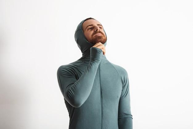 Młody, brodaty atleta zapina zamek błyskawiczny, nosząc kaptur swojego uschniętego termicznego zestawu snowboardowego