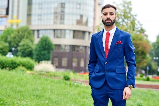 Młody brodaty biznesmen arabski w garniturze stwarzających lato na zewnątrz