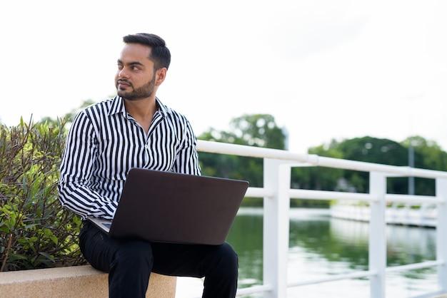 Młody brodaty biznesmen indyjski relaks w parku