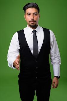 Młody brodaty biznesmen iranu na zielono