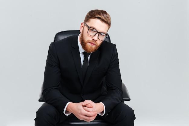 Młody brodaty biznesmen w okularach i czarnym garniturze, siedząc na fotelu i patrząc na kamerę