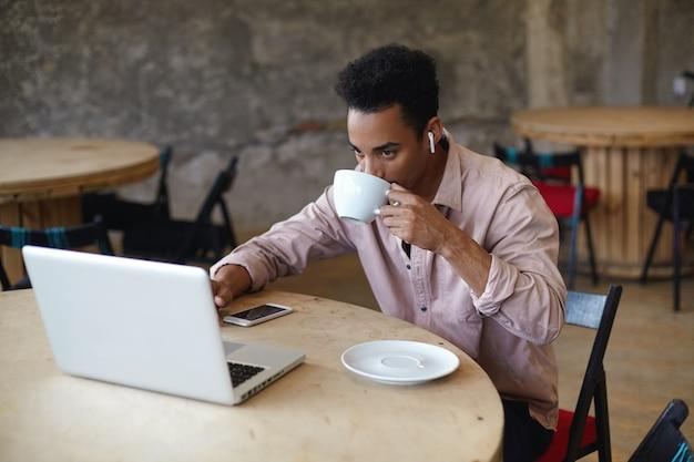 Młody brodaty ciemnoskóry biznesmen z krótką fryzurą pije kawę w miejskiej kawiarni, przygotowując materiały na swoim laptopie na spotkanie z klientami, siedząc przy okrągłym drewnianym stole w beżowej koszuli