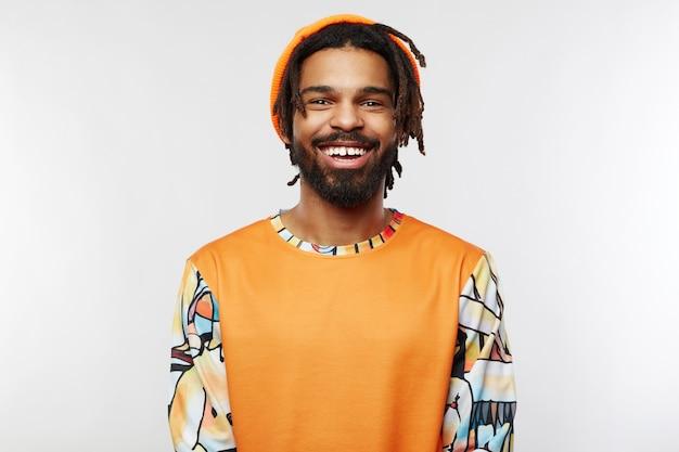 Młody brodaty ciemnoskóry mężczyzna w pomarańczowym kapeluszu na białym tle