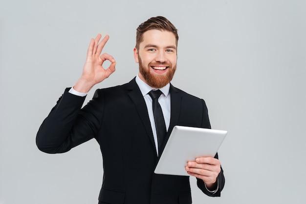 Młody brodaty człowiek biznesu w czarnym garniturze, trzymając komputer typu tablet i pokazując znak ok jako
