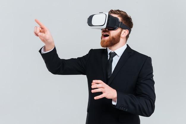 Młody brodaty człowiek biznesu w garniturze za pomocą urządzenia wirtualnej rzeczywistości. na białym tle szarym tle